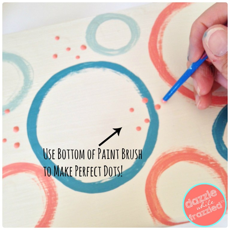 Use the bottom end of a paint brush to make perfectly round polka dots on DIY kids step stool makeover with paint