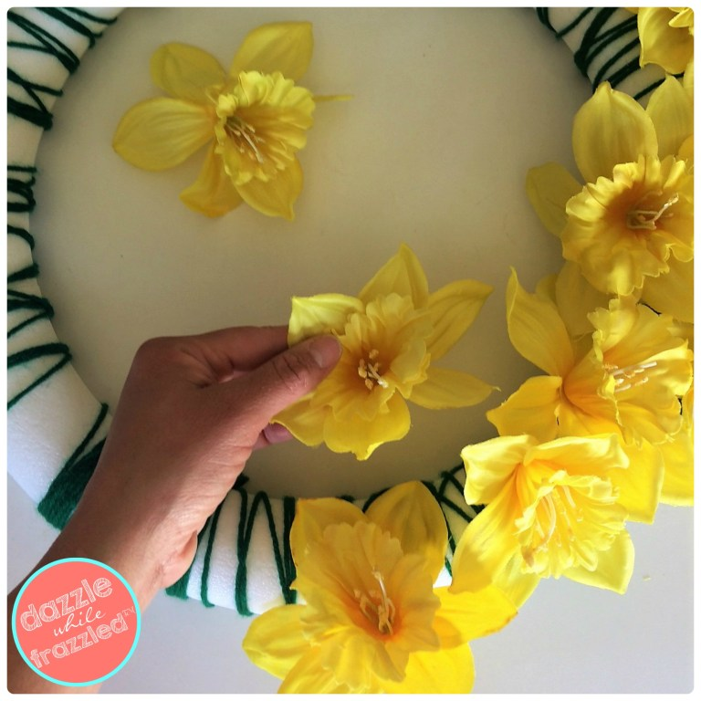 Arrange faux daffodils in a whimsical manner onto a green yarn foam wreath for spring front door decor.