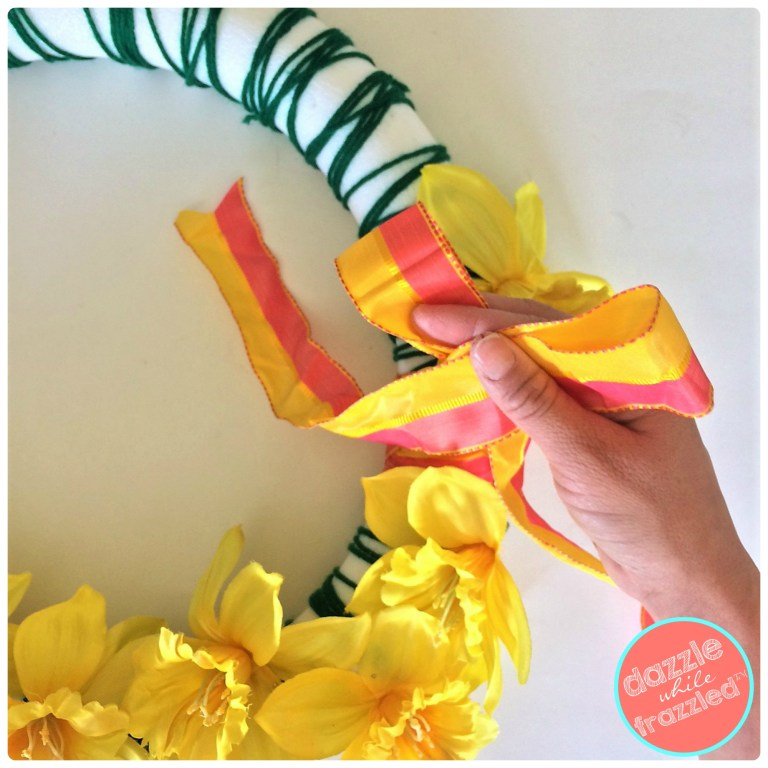 Add a colorful large ribbon to a green yarn spring daffodil wreath.