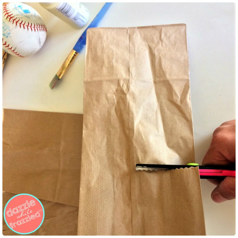 Cut a brown paper lunch sack in half to make DIY baseball snack bags for kids