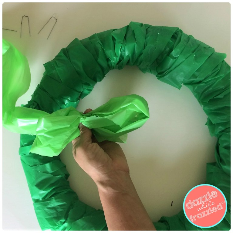 Use lime green plastic tablecloth for DIY oversized Christmas bow for cheap poinsettia door wreath.