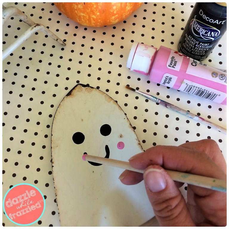 Use the back of a paint brush to make perfectly round dots. DIY garden shovel Halloween ghost decoration.