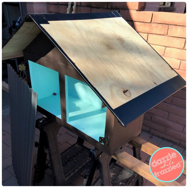 Apply Gorilla Glue Waterproof Patch and Seal Tape to pitched roof and sides of plywood roof on DIY Little Free Library.
