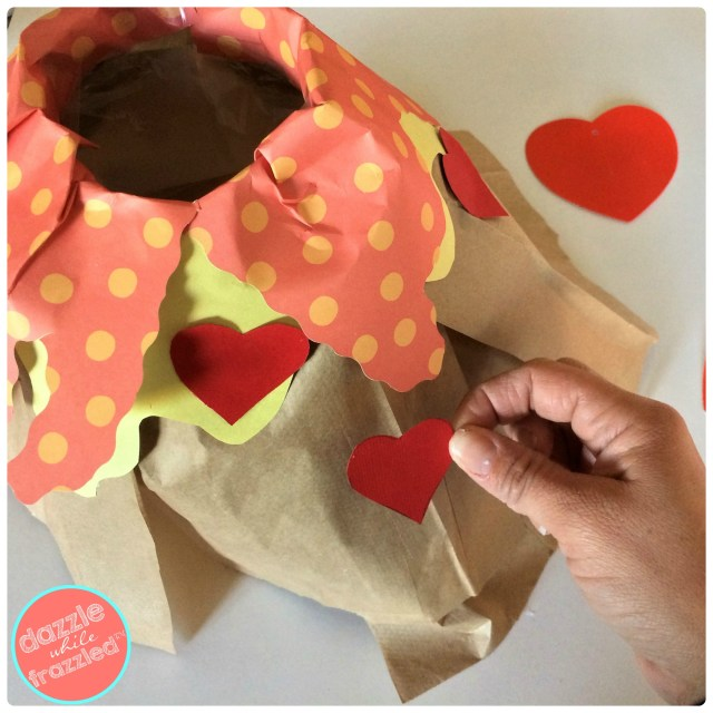 Cover sides of brown paper volcano with heart stickers or scrapbook paper heart cutouts for DIY kids Valentine's Day volcano card box holder.