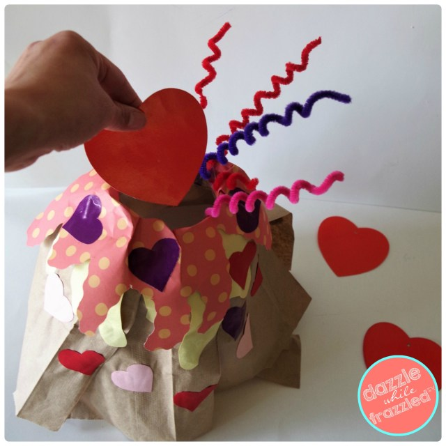 Put kids Valentine's cards from classroom exchange in DIY brown paper bag milk jug volcano Valentine's Day card box holder.