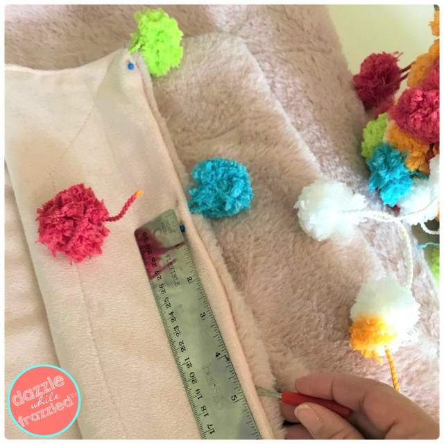 Use seam ripper to rip out seam in blanket throw to insert pom poms from Pomp a Doodle yarn. Secure with sewing straight pin.