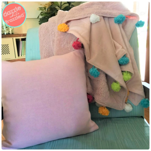 Use Pomp a Doodle yarn to add cute pom poms to blanket throw.