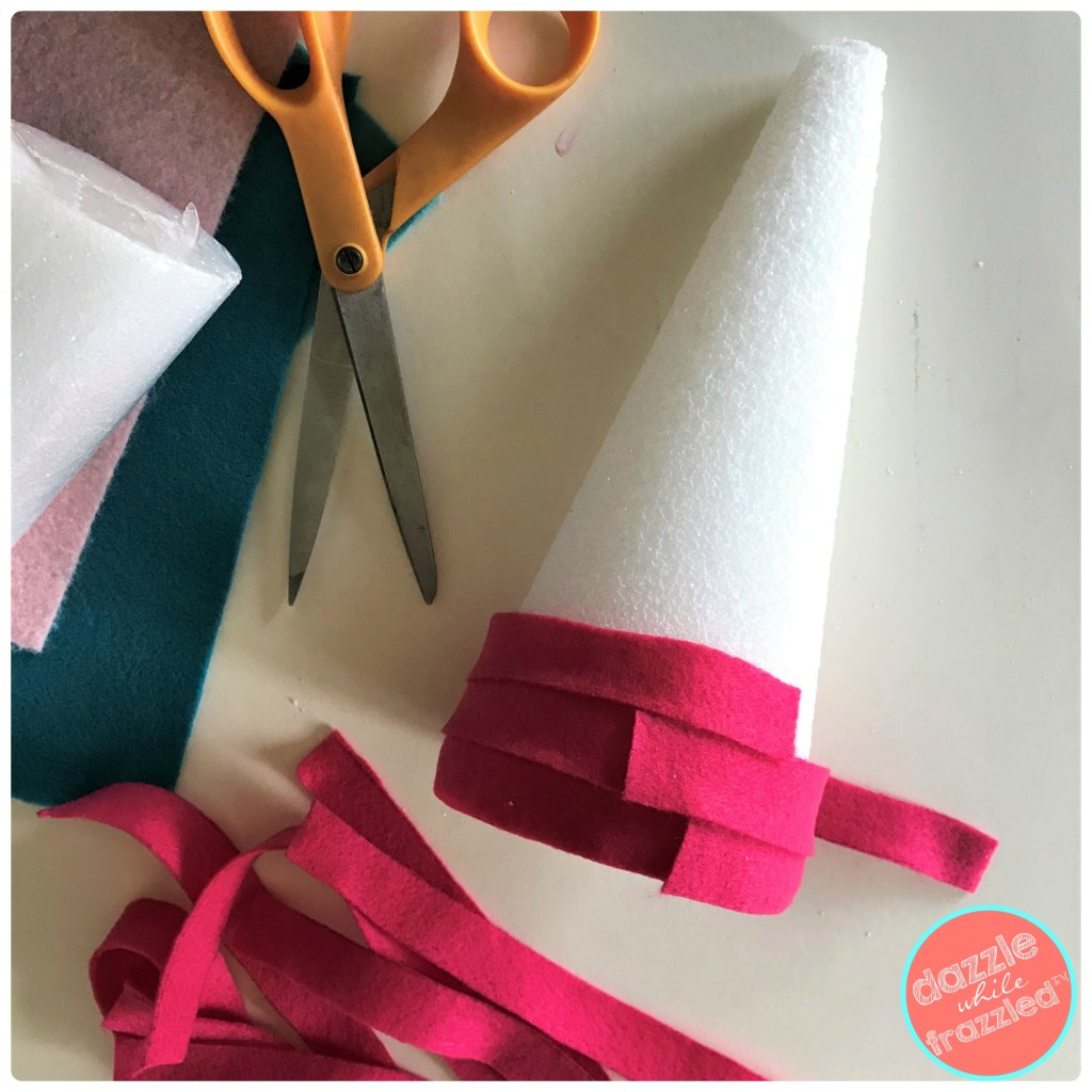 """Cut 1"""" strips from felt and cover styrofoam cone with felt strips for DIY tabletop Christmas trees."""