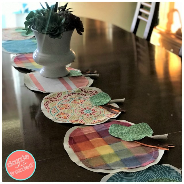 Set your Thanksgiving table with farmhouse-inspired fabric pumpkin table runner using fabric scraps and grosgrain ribbon.