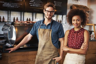 Portrait of a female and male barista standing inside their coffee house with copyspace