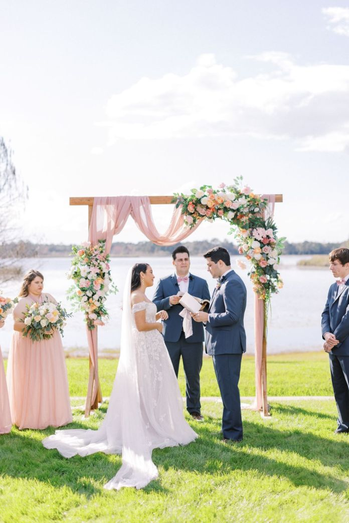 The bride and groom are married by the groom's brother at their light and airy spring wedding