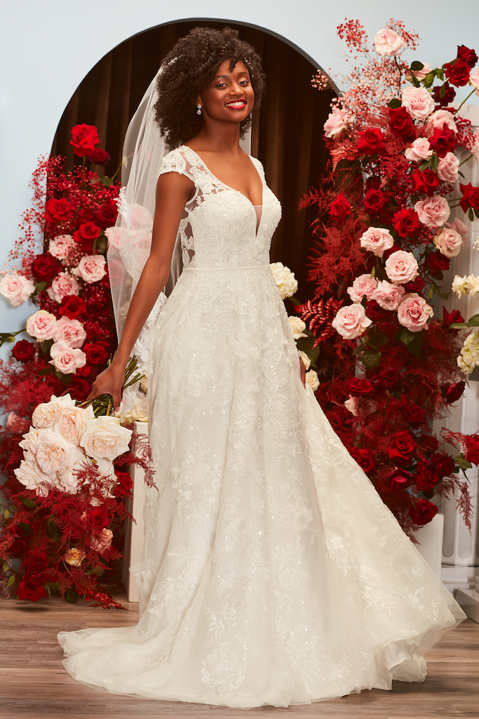 Bride is wearing a fall wedding dress 2021, embellished with lace and parkles