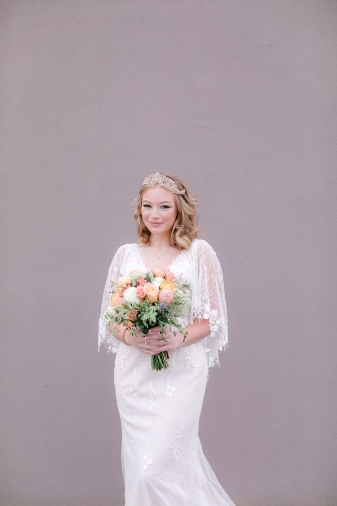 Bride in a boho wedding dress with a bouquet of pastel flowers