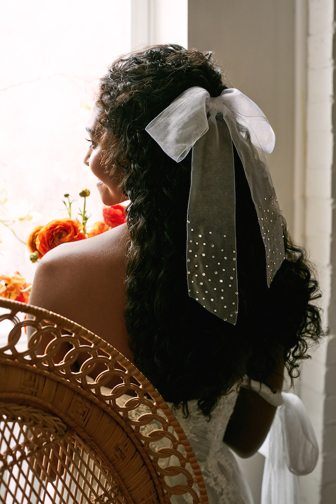 Bride wears a tulle bow with scattered crystals