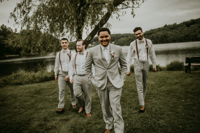 Groom and groomsmen at a rustic outdoor wedding