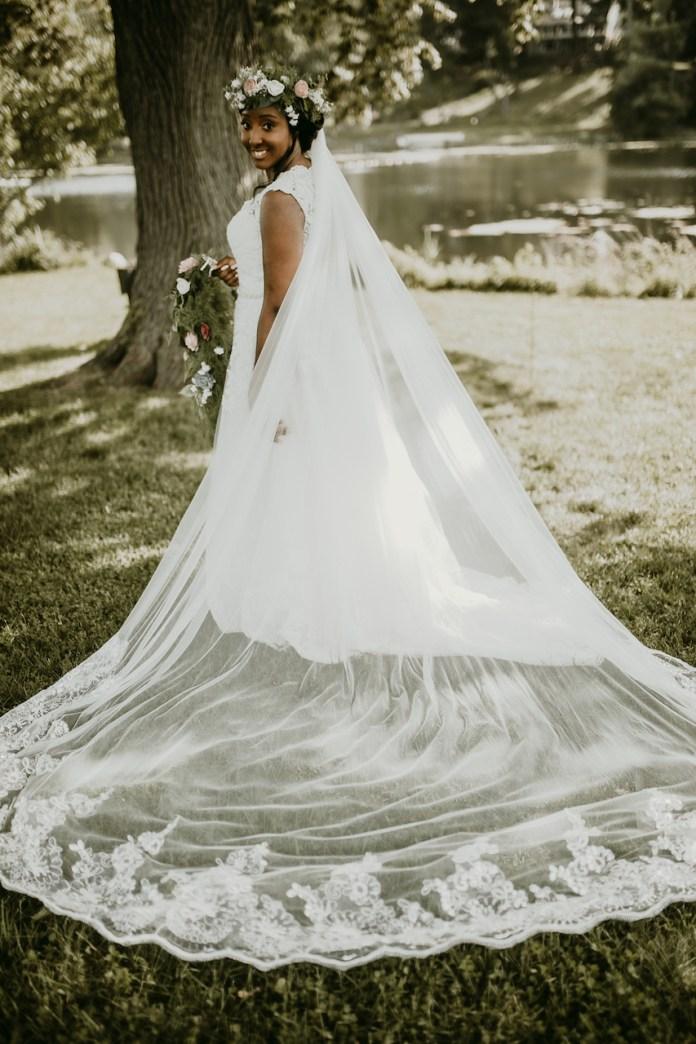 Bride in lace wedding dress at rustic outdoor wedding