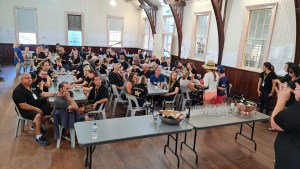 Campers in the main hall enjoying wine tasting siting at long tables