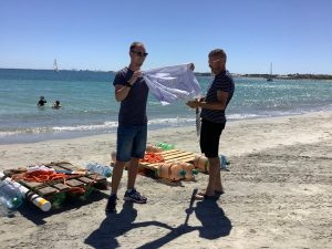 2 Rafts on the beach made by campers. Paul and Darren preparing to race the rafts.