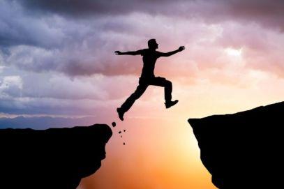 a person jumping between cliffs