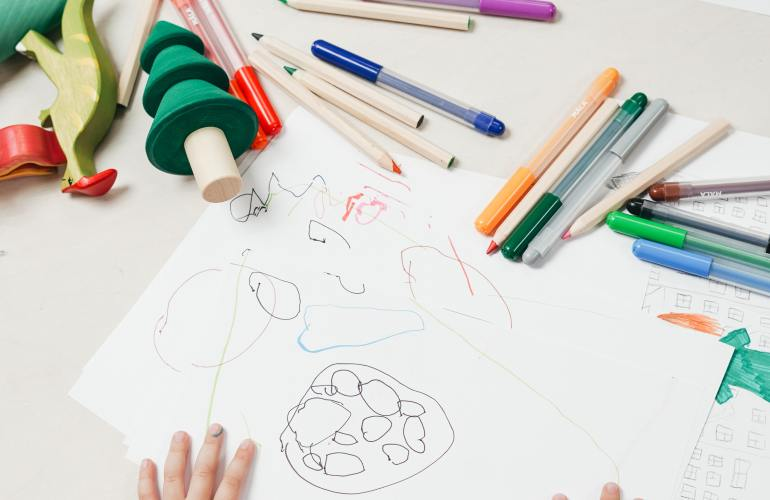 Kid drawing on white table