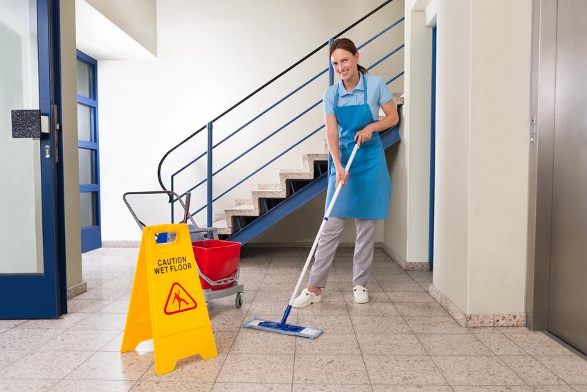Frau beim Treppenhausreinigen