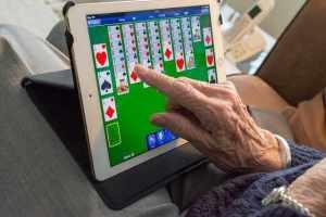 Oma spielt Karten am Tablett
