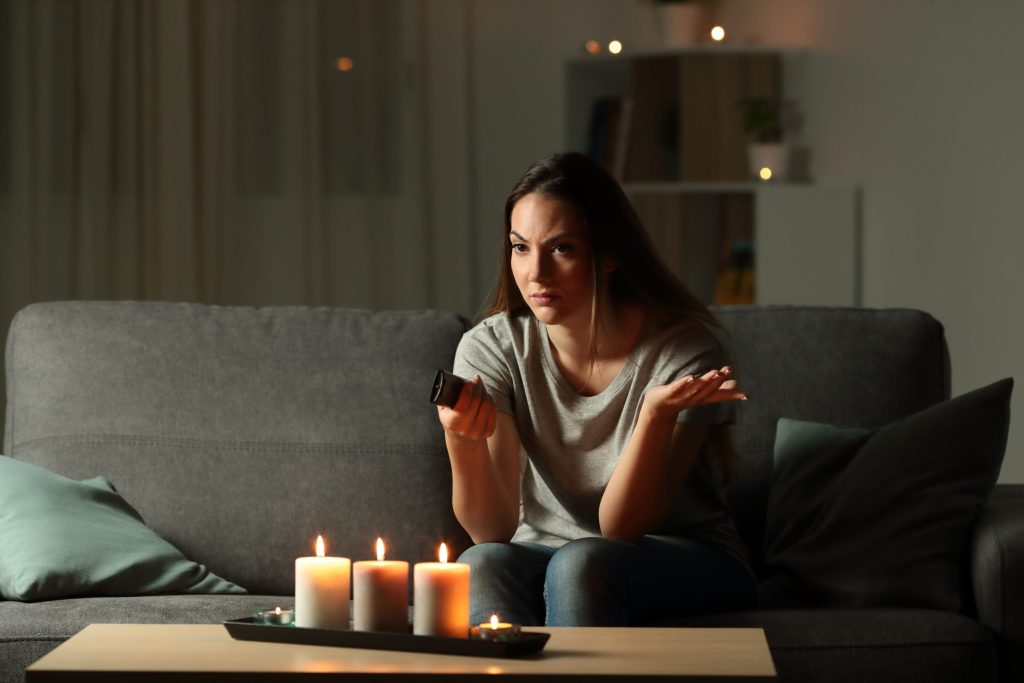 Image: A frustrated woman surrounded by lit candles, dealing with a power outage.