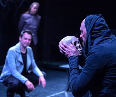 (r) Jim Jorgensen as the Gravedigger, with Marcus Kyd as Hamlet and Esther Williamson as Ophelia in background. Hamlet, the First Quarto. (Photo: C. Stanley Photography)