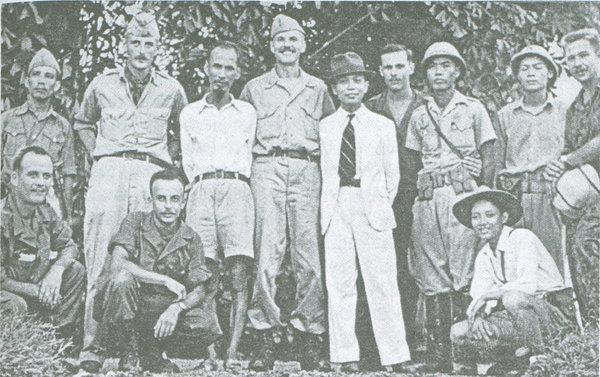"""Thành viên của Toán Con Nai của Cơ quan Tình báo Trung ương của Mỹ thời Đệ nhị Thế chiến (O.S.S. - Office of Strategic Services) với Hồ Chí Minh, (đứng thứ ba từ trái sang) """"ông Văn"""" (đeo cà vạt) và một số cán bộ Việt Minh khi được tình báo huấn luyện quân sự hồi 1945. Henry Prunier là người thứ tư từ phải (sau lưng V.N. Giáp). Nguồn: TNYT."""
