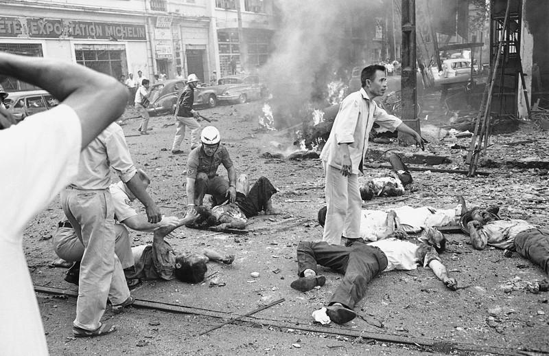 Việt bị thương nhận được viện trợ như chúng nằm trên các đường phố sau khi một quả bom phát nổ bên ngoài Đại sứ quán Mỹ ở Sài Gòn, Việt Nam, ngày 30 tháng 3, 1965. Khói tăng từ đống đổ nát trong nền. Ít nhất hai người Mỹ và một số Việt thiệt mạng trong vụ đánh bom. Ảnh AP Photo / Horst Faas