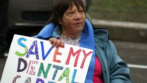 "Advocate with developmental disability holds sign that reads, ""Save My Dental"" in protest."