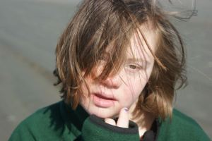 teenager with down syndrome looks out over a windy beach