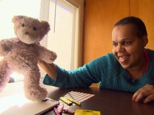 Photo of Laura Gholston holding up a teddy bear