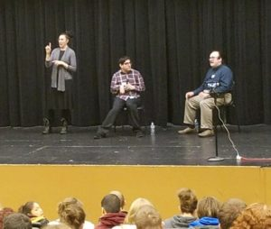 Tim McCue and Noah Seidel standing on a stage with an interpreter, in front of an audience.