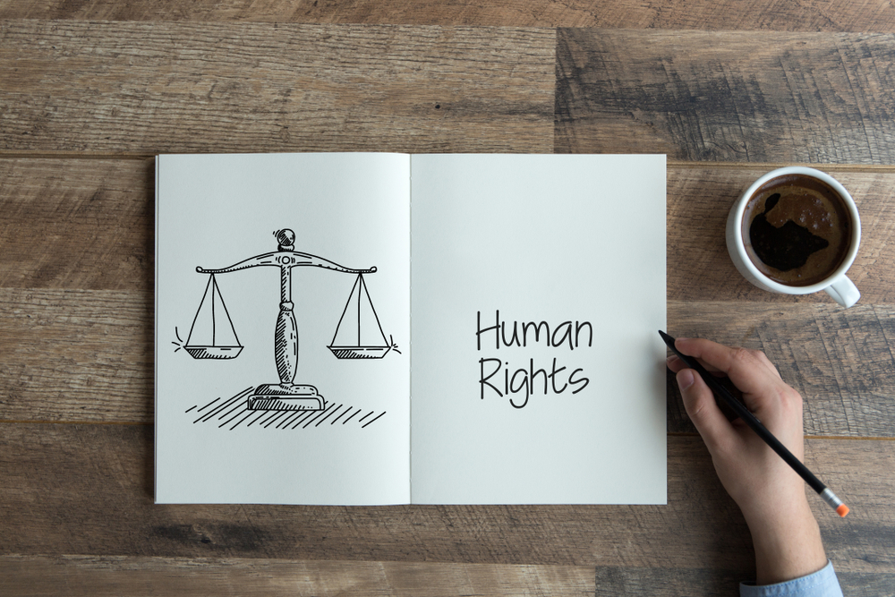 """Photo of a notebook showing scales and the words """"human rights"""" on a wood table. There is a hand holding a pen and a cup of coffee next to it."""
