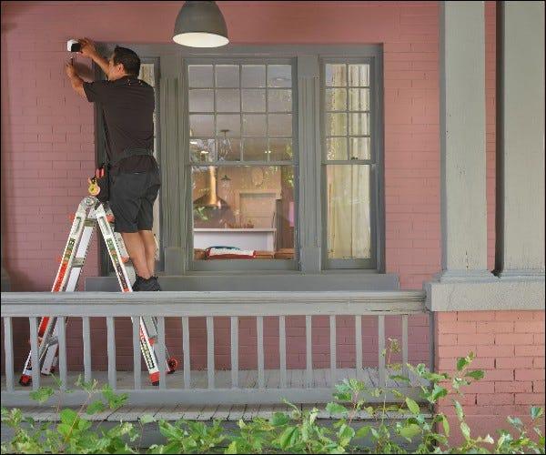 Mann installiert Kamera außerhalb des Hauses