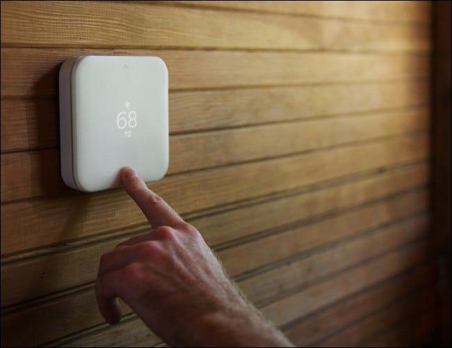 Quadratischer weißer Thermostat an Holzwand