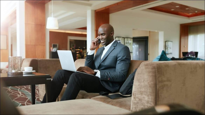 Ein Geschäftsmann sitzt in einer Hotellobby und arbeitet an einem Laptop.