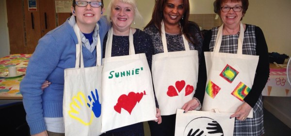 4 people with decorated aprons