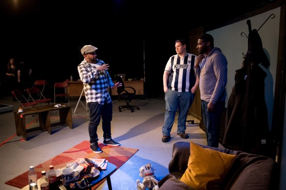 There are three men in this picture, On the left hand side Rinkoo is directing using hand movement that has purpose and two men are looking at Rinkoo's hands and face with interest. In the middle is a young man who is overweight and sporting a West Bromwich Albion football shirt. The man on the right is wearing a hoody