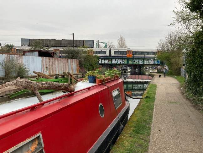 A picture of a canal boat with a train passing over a bridge above it