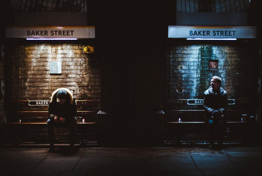 Two commuters waiting for a train at Baker Street station