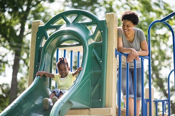 mother pushing child down slide