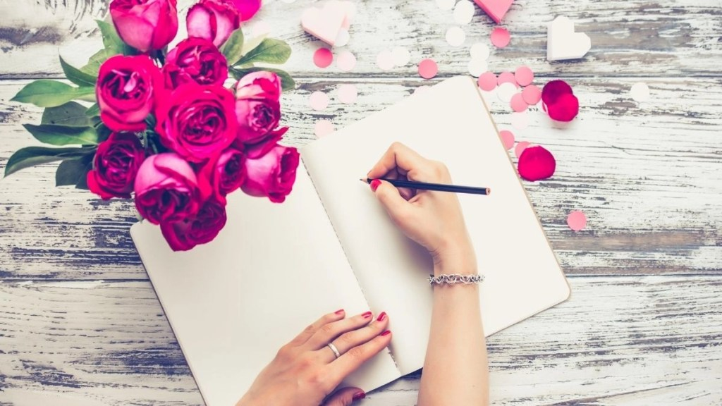 Hands with pen performing Law of Attraction Scripting in a journal.