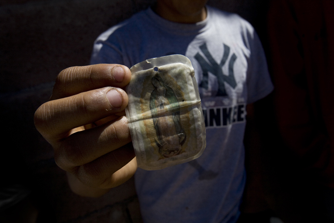 A man waiting for deported family displays a Virgen de Guadalupe prayer card, wrinkled from being inside of his wallet, at the U.S.-Mexico border wall in Nogales, Sonora