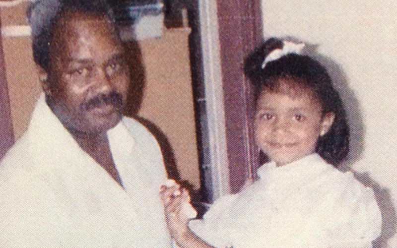 An African American father with a mustache and daughter wearing a white dress and white bow in her hair