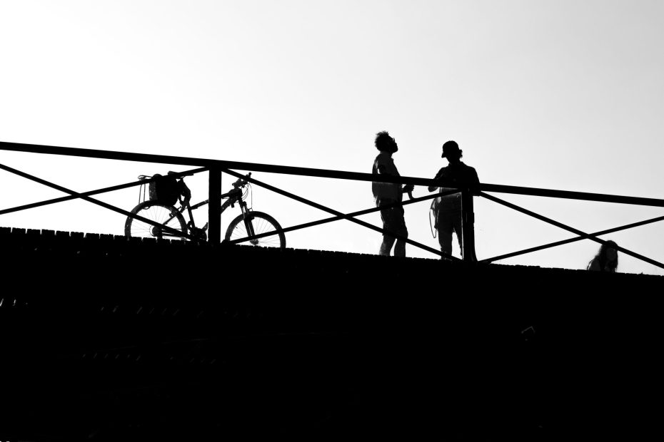 Photo of two people talking on a bridge next to a bike.