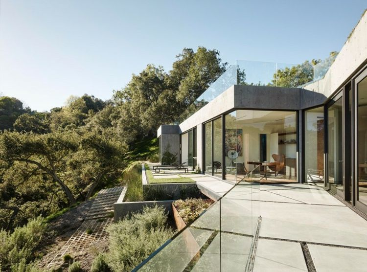 Haus aus Glas und Beton auf einem Hgel mit Eichen