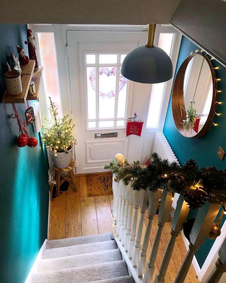 Weihnachtsdeko im Treppenhaus kleiner Tannenbaum im Topf Tannengirlanden und Lichterketten