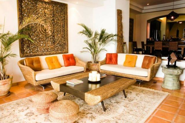 decoration-salon-coussins-orange-jaune-canapés-rotin-palmiers-tableau-exotique
